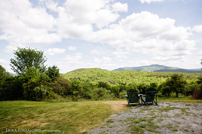 A pair of Adirondack chairs overlooking the view of Mt. Sunapee