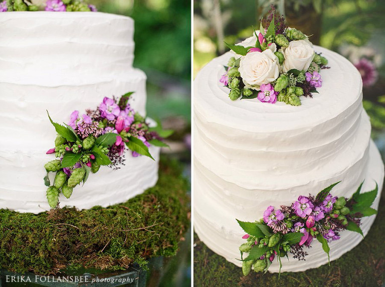 rough frosted white cake with white roses and green hops