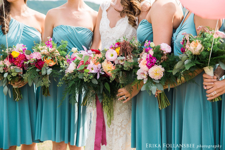 bride and bridesmaids in blue dresses with large, colorful bouquets