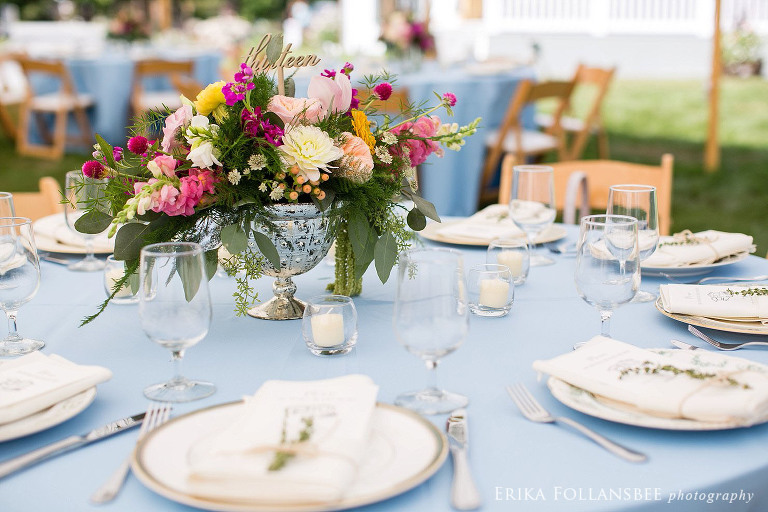 Colorful centerpieces on powder blue tablecloths with mismatched china plates