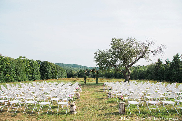 Wedding ceremony in an open field with a single apple tree, white birch arbor, and views of rolling hills | Henniker, NH