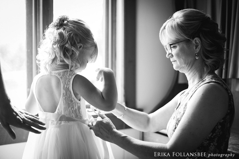 Tying the ribbon sash on the flower girl's dress