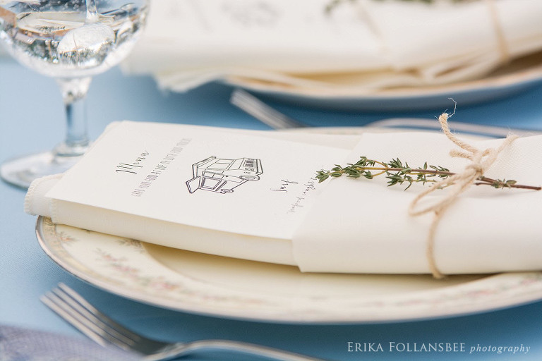 wedding menu tucked into napkin tied with twine and a sprig of thyme