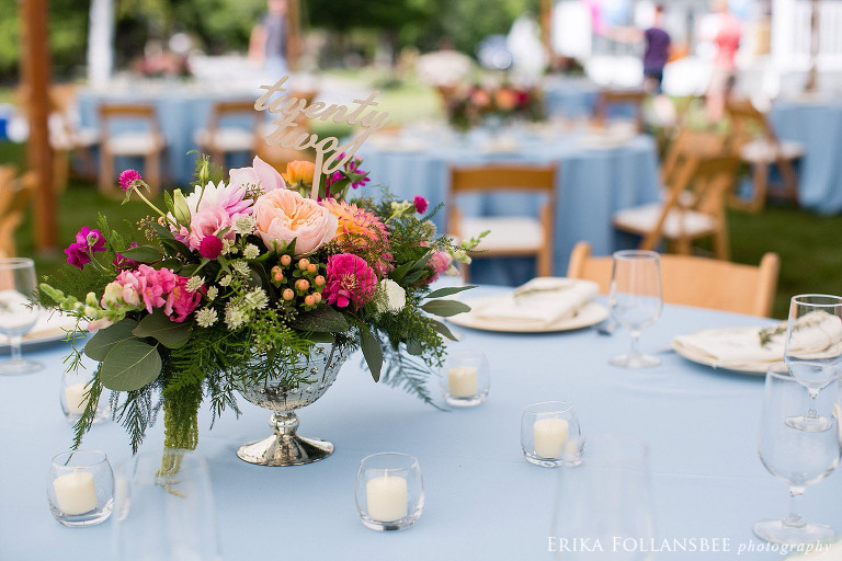 Colorful centerpieces by Sorella Flower Company on blue tablecloths with mismatched china plates