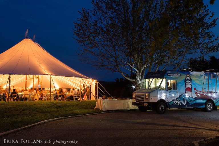 Nighttime photo of the tent all lit up with Cod Squad food truck parked in front.