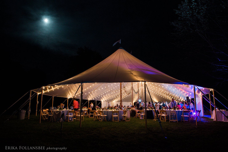 Night photo of the tent lit up by bistro lights
